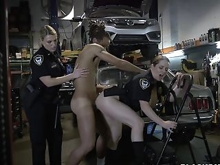 Predominant Voluptious Police Officer With Her Hair Tied Wearing Her Blue Uniform Kneels By The Old-school Gray Car In The Autoshop And Plays With Sus