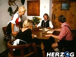 Horny Hun With Moustaches Drilling Hot Blondie On The Table While His Mate Fucking Dark-haired Cutie