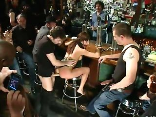 Wild Black-haired Buxom With Pierced Nips Gets Tethered, Fisted And Deep Gullet Fucked With Thick Sausages In The Bar